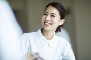 打ち合わせをする笑顔の女性看護師の写真素材 [FYI04930522]