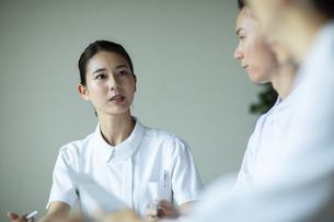 打ち合わせで患者の病状を説明をする女性看護師の写真素材 [FYI04930523]