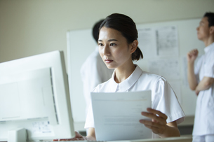 資料を見ながらPCを操作する女性看護師の写真素材 [FYI04930544]