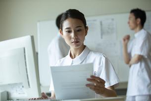 資料を見ながらPCを操作する女性看護師の写真素材 [FYI04930550]