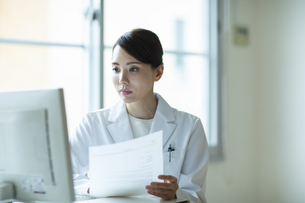 資料を見ながらPCを操作する女医の写真素材 [FYI04930553]