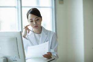 資料を見ながらPCを操作する女医の写真素材 [FYI04930554]