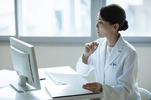 資料を見ながらPCを操作する女医の写真素材 [FYI04930558]