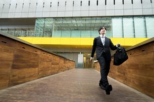 元気に歩くスーツ姿の男性(ビジネスイメージ)の写真素材 [FYI04932427]