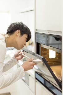 オーブンを開ける若い男性の写真素材 [FYI04932471]