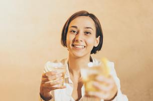 アルコール飲料(お酒・ハイボール・ウィスキー)を手渡す女性の写真素材 [FYI04933359]