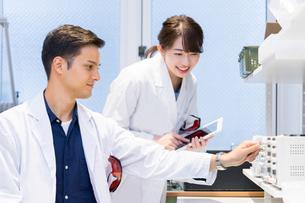 実験室で研究開発・解析・調査をする白衣の男性と女性の写真素材 [FYI04934409]