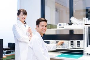 実験室で研究開発・解析・調査をする白衣の男性と女性(カメラ目線)の写真素材 [FYI04934411]
