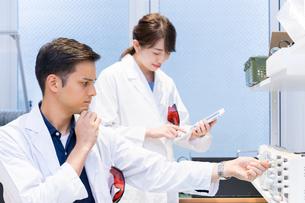 実験室で研究開発・解析・調査をする白衣の男性と女性の写真素材 [FYI04934414]