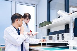 実験室で研究開発・解析・調査をする白衣の男性と女性の写真素材 [FYI04934415]