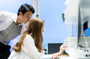 実験室で研究開発・解析・調査をする白衣の男性と女性の写真素材 [FYI04934426]