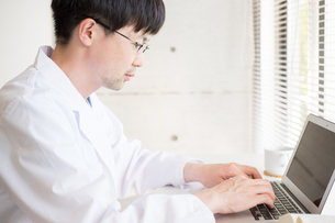 デスクワークをする白衣の男性の写真素材 [FYI04938295]
