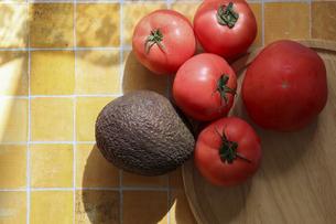 タイルパターン背景のアボカドとトマトの写真素材 [FYI04938598]