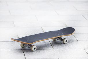 公園のコンクリートに置かれたスケートボードの写真素材 [FYI04938861]