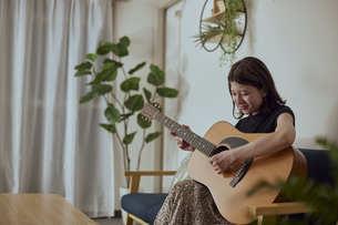 リビングでギターを弾く若い日本人女性の写真素材 [FYI04940009]