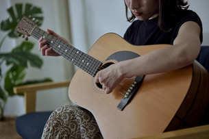 リビングでギターを弾く若い日本人女性の写真素材 [FYI04940011]