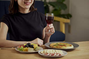家で一人でお酒を楽しむ若い日本人女性の写真素材 [FYI04940019]