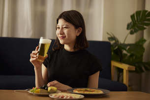 家で一人でお酒を楽しむ若い日本人女性の写真素材 [FYI04940020]