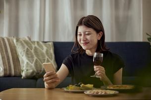 家で一人でお酒を楽しむ若い日本人女性の写真素材 [FYI04940021]