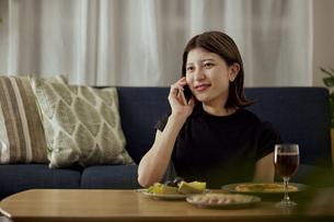 家で一人でお酒を楽しむ若い日本人女性の写真素材 [FYI04940022]