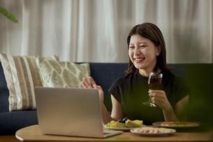 家で一人でお酒を楽しむ若い日本人女性の写真素材 [FYI04940023]