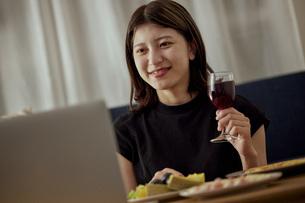 家で一人でお酒を楽しむ若い日本人女性の写真素材 [FYI04940024]