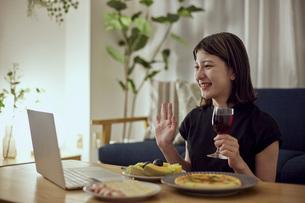 家で一人でお酒を楽しむ若い日本人女性の写真素材 [FYI04940025]