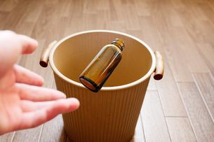 栄養ドリンクの空き瓶をゴミ箱に投げずてるの写真素材 [FYI04940552]