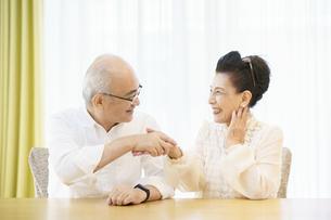リビングルームで仲良く談笑するシニア夫婦の写真素材 [FYI04942395]
