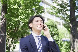 外で電話するビジネスマンの写真素材 [FYI04942425]