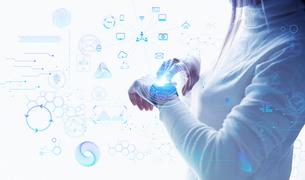 白い明るい背景に佇む女性とスマートウォッチのテクノロジーのアイコンとホログラムの写真素材 [FYI04944315]