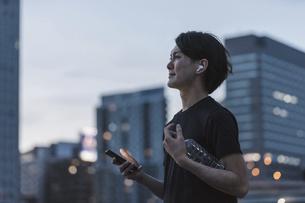 屋外で音楽を聞きながらランニングの準備をする若い男性の写真素材 [FYI04945344]