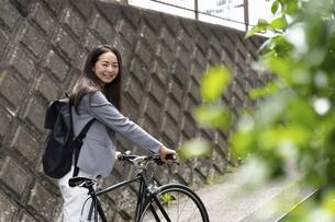 笑顔で振り向く女性・自転車の通勤イメージの写真素材 [FYI04945759]