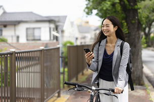 笑顔で自転車通勤する女性・スマートフォンの操作の写真素材 [FYI04945762]