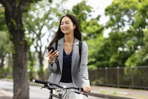 笑顔で自転車通勤する女性・スマートフォンの操作の写真素材 [FYI04945764]