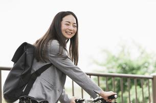 笑顔で自転車通勤する女性の写真素材 [FYI04945772]