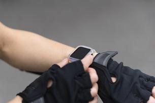手元のスマートウォッチを操作する女性・ボティパーツの写真素材 [FYI04945778]