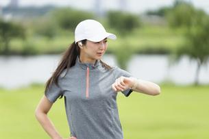スマートウォッチを見てランニングをする女性の写真素材 [FYI04945789]