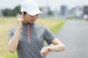 スマートウォッチを見てランニングをする女性の写真素材 [FYI04945797]