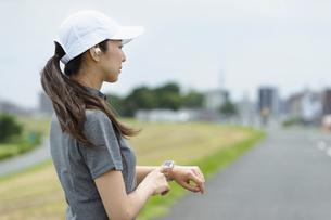 スマートウォッチを見てランニングをする女性の写真素材 [FYI04945801]