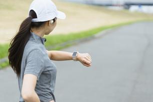 スマートウォッチを見てランニングをする女性の写真素材 [FYI04945987]