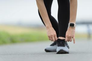 靴紐を結ぶびトレーニングの準備(スマートウォッチをつけた手元・女性)の写真素材 [FYI04946000]