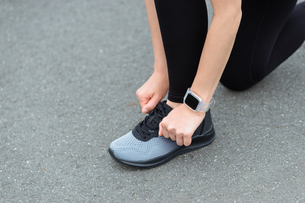 靴紐を結ぶびトレーニングの準備(スマートウォッチをつけた手元・女性)の写真素材 [FYI04946006]