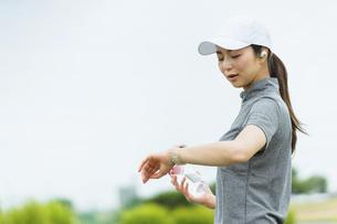 スマートウォッチを見てランニングをする女性の写真素材 [FYI04946015]
