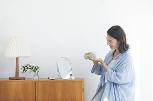 部屋で鏡を見ながらスキンケアをする女性の写真素材 [FYI04946095]