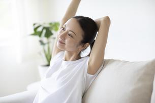 ソファに座ってリラックスする女性の写真素材 [FYI04947624]