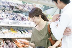 スーパーで人参を手に取る女性の写真素材 [FYI04948013]