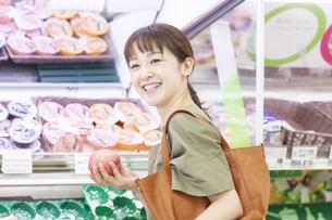 青果コーナーでりんごを持つ女性の写真素材 [FYI04948014]
