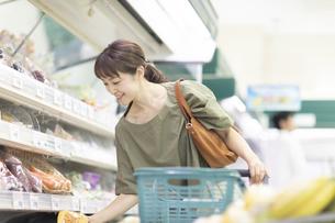 スーパーで商品を手に取る女性の写真素材 [FYI04948019]