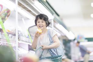 スーパーでレモンを手に取るシニア女性の写真素材 [FYI04948021]